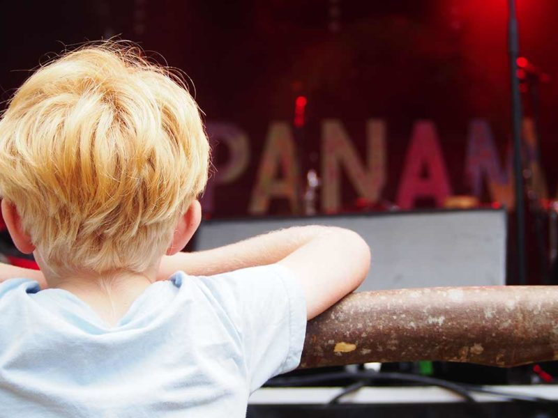 Young child leaning on fence looking at Panama sign